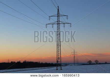 Winter landscape with fields and meadows  / Sunset in the winter / High-voltage masts.