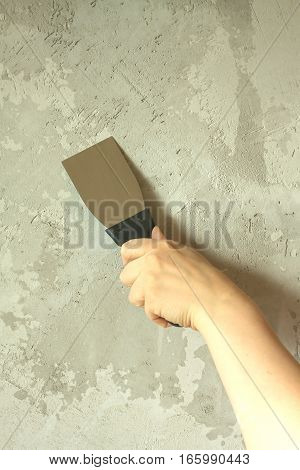 Woman's hand with a spatula wall plasters in room during repair vertical photo