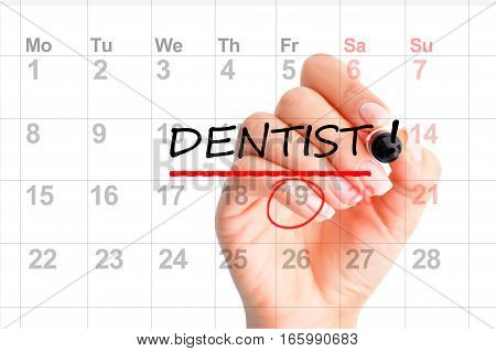 Dentist appointment reminder on calendar planner with woman hand