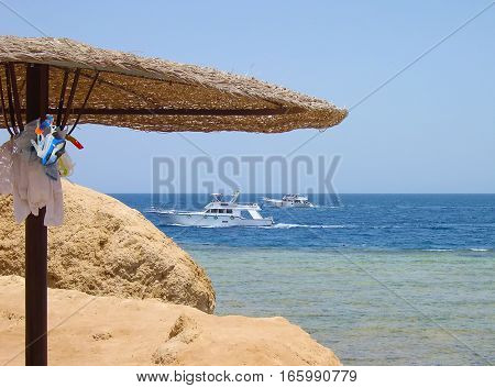 Umbrella with snorkeling equipment on the beach. Tourism background for travel, vacation and holidays. Two white yachts sail by sea.