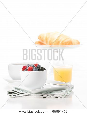 Small bowl of fresh berries served with croissant coffee and orange juice.