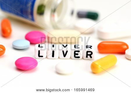 Liver problems concept with close-up of colorful medical pills and liver word on white background