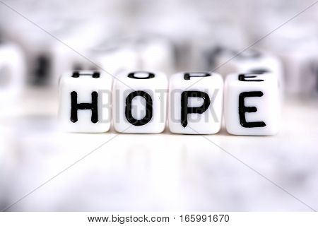 Hope word made from plastic alphabet blocks, stands in white background.
