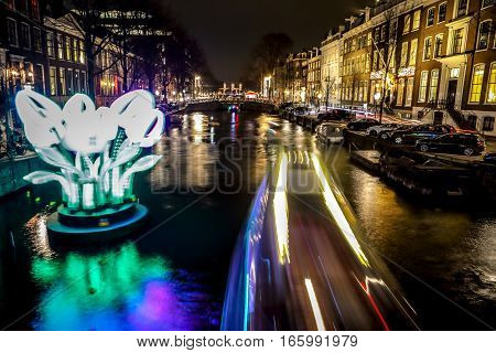 AMSTERDAM NETHERLANDS - JANUARY 11 2017: Cruise boats rush in night canals. Light installations on night canals of Amsterdam within Light Festival. January 11 2017 in Amsterdam - Netherland.