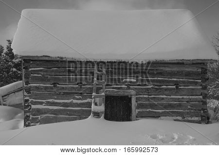 Small snowflakes speckle this black and white winter image or a rural log cabin ban on a farm. Snow on the roof and on the ground