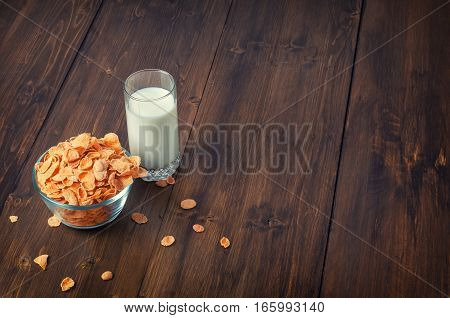 Tasty corn flakes in bowl with glass of milk. Rustic wooden background. Healthy crispy breakfast snack. Place for text. Top view, flat lay. Text space.