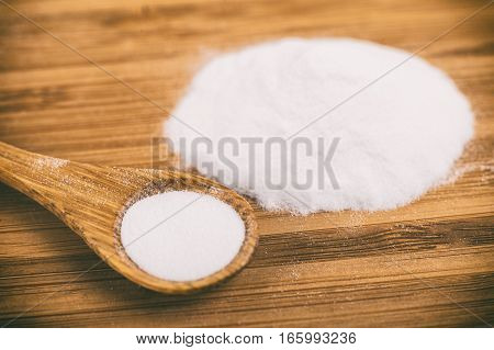 Baking soda in a wooden spoon on a wooden board