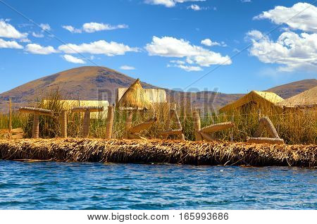 Manmade floating island with a sign spelling out Titikaka on Lake Titicaca in Peru