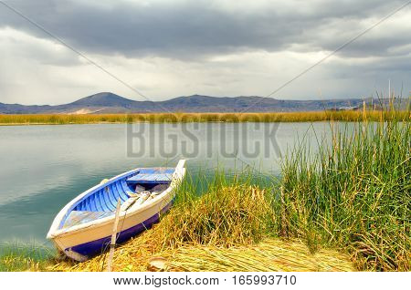 Boat on the shore of a manmade floating island on Lake Titicaca in Peru