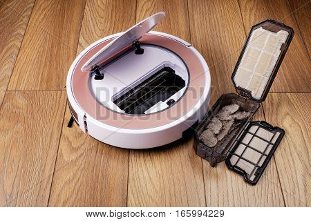 robotic vacuum cleaner on laminate wood floor smart cleaning technology, cleaning the dirt container