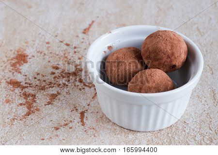 Photo of handmade vegan date balls. Sweetmeat with the coca powder in the white bowl.