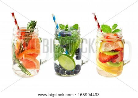 Three Types Of Fruit Detox Water In Mason Jar Glasses With Straws Isolated On A White Background