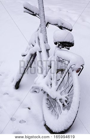 Angled rear view of a bicycle covered in freshly fallen snow locked to a sign pole on a street in Montreal Quebec on a bright November day.
