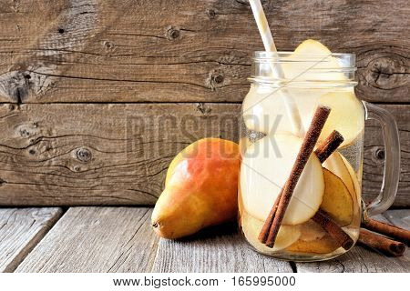 Pear, Ginger, Cinnamon Detox Water In A Mason Jar Glass With Straw Against A Rustic Wood Background