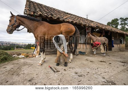 July 22, 2016 Cuenca Ecuador: men changing horse shoes at stables at a local hacienda