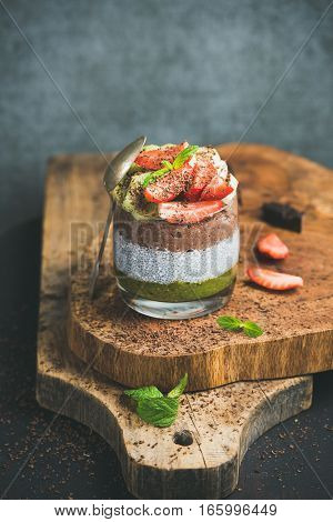 Healthy breakfast. Matcha, almond milk, cocoa chia seed pudding with fresh fruit, berries, mint and chocolate in glass over wooden board, grey wall background, selective focus. Clean eating concept