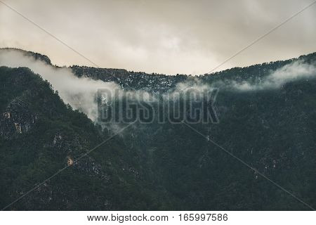 Green slopes of the Taurus mountains range covered with snow and clouds in winter. Southern Turkey, Alanya, Dim Cay river valley