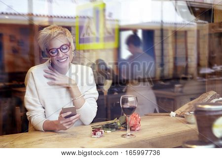 Beautiful blonde woman wearing eyeglasses messaging by mobile phone in cafe. Got a love message. Present box and rose flowers on wooden table. Romantic breakfast for a date or St. Valentine's Day.