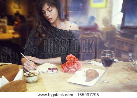 Beautiful european woman with long hair writing in notebook near window in cafe. Romantique breakfast date or St. Valentine's Day. Present box and rose flowers.