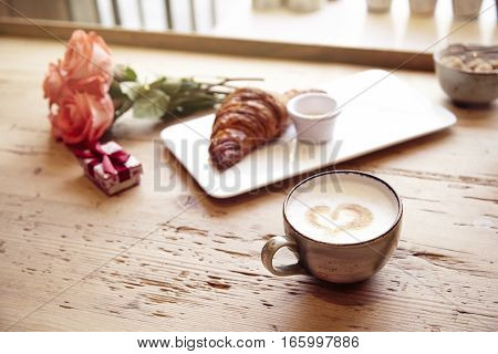 Romantic breakfast Valentine's Day celebrating. Present box rose flowers fresh croissant coffee on wooden table. Focus on cup. Daylight from window.