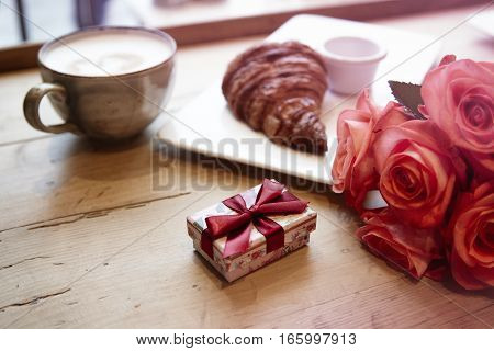 Romantic breakfast for Valentine's Day celebrate. Present box rose flowers fresh croissant coffeeon wooden table.