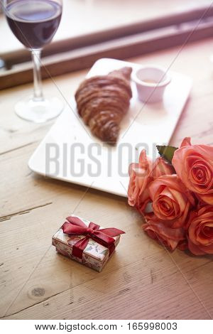 Romantic breakfast for Valentine's Day celebrate concept. Fresh bakery croissant red wine rose flowers on wooden table.