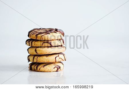 Stack of butter cookies with chocolate drizzle isolated on on a white background. Copyspace for text.