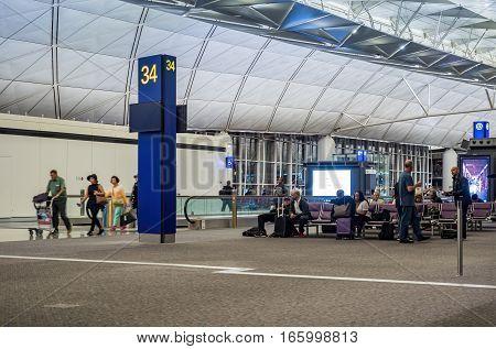 Hong Kong, China - Oct 30, 2016: At Hong Kong International Airport. Passengers walking and waiting around Terminal 34.