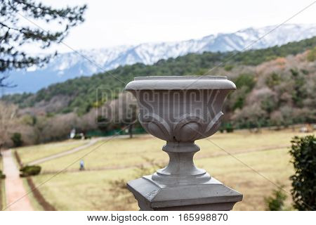 Large Stone Flower Vase Stands On A Ladder In The Park.