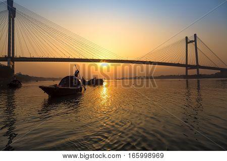 Sunset over Vidyasagar bridge with wooden boats on river Hooghly, Kolkata, India.