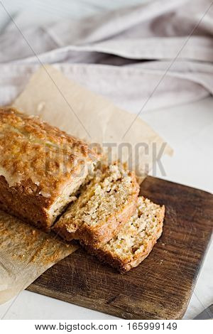 Glazed applesauce oatmeal bread on a white marble table. Ideal healthy breakfast with coffee and loaf cake.