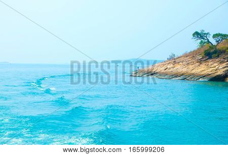 Single man on a secluded rocky island in the sea. Crystal blue waves. Thailand