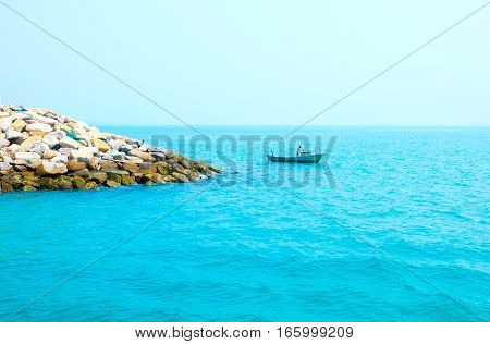 Man in a longtale boat in the turquoise sea. Secluded rocky island. Thailand