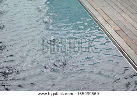 Reflective Pool Edge Detail. Steel edge. Timber Deck. Water