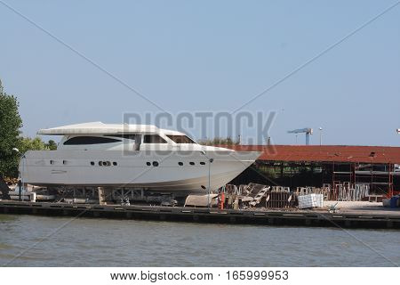 Big motorboat in shipyard outside the water for repairs.