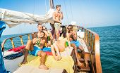Happy multiracial friends drinking beer and having fun at sail boat party tour - Friendship concept with young multi racial people toasting together on sailboat - Travel lifestyle exclusive location poster