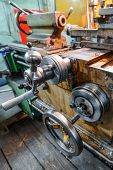 The carriage slide. Mechanical wheel carriage control. Vintage metal cutting lathe. The old mechanical cutting equipment. poster