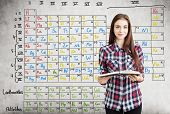 Close up of a nerdy teen girl in a checkered shirt holding an open book near a concrete wall with Mendeleev periodic table on it. poster