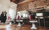Horizontal shot of empty chairs in retro styled barbershop. Hair salon interior. poster