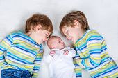 Two happy little preschool kids boys with newborn baby girl, cute sister. Siblings, , twins children and baby playing together. Kids bonding. Family of three, love. poster