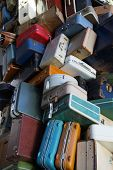 Pile of various styles of old luggage at airport or train station poster