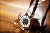 Hour glass or sand timer with vintage pocket watch, symbols of time with copy space poster