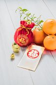 "Chinese New yeargolden envelope packet (ang pow) and red felt fabric bag with gold ingots and oranges and flower on white wood table topChinese Language on envelop mean Happiness and on ingot mean ""Wealthy"". poster"