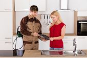 Young Smiling Woman Signing Invoice From Exterminator Worker After Pest Control Work In House Kitchen poster