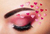 Eye make-up girl with a heart. Valentine's day makeup. Beauty fashion. Eyelashes. Cosmetic Eyeshadow. Makeup detail. Creative woman holiday make-up poster