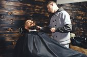 Young Bearded Man Getting Beard Haircut By Barber While Sitting In Chair At Barbershop. Barbershop Theme poster