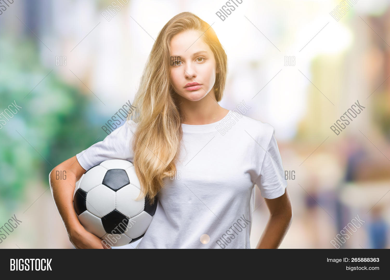 d4424dd5d Young beautiful blonde woman holding soccer ball over isolated background  with a confident expression on smart