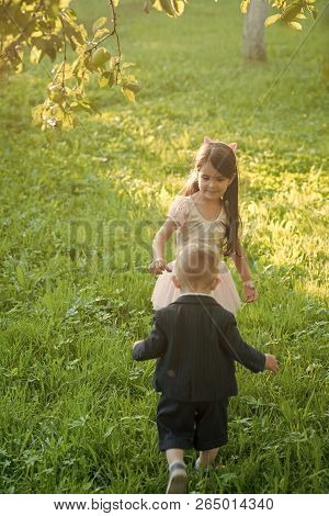 Little Boy And Girl Play On Green Grass, Energy. Children, Childhood, Family. Brother And Sister Hav