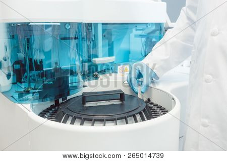 Doctor putting tubes of blood in centrifugal machine for testing and analyzing