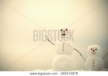 Happy Holiday And Celebration. Snowman Family In Winter Outdoor. New Year Mother Or Father And Child